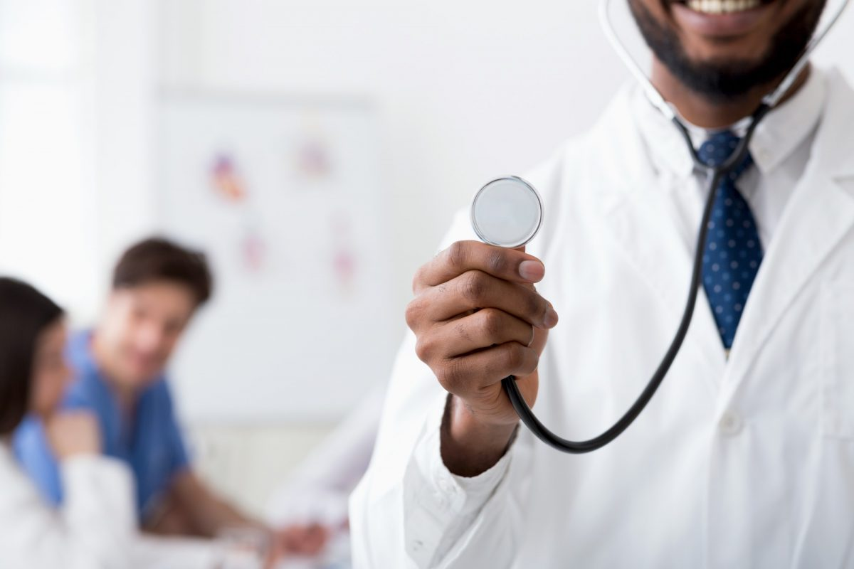 Doctor with stethoscope, medical staff working on background